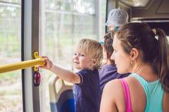 Mamman och sonen passerar bussen Resa med barnbegrepp royaltyfria bilder