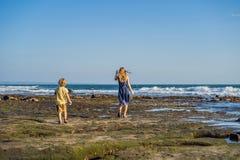 Mamman och sonen promenerar den kosmiska Bali stranden Stående t royaltyfri foto