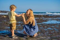 Mamman och sonen promenerar den kosmiska Bali stranden Stående t royaltyfri bild