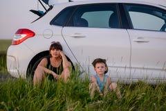 Mamman och sonen sitter bredvid bilen, medan vänta royaltyfria foton