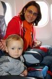 Mamman och sonen sitter inom ett flygplan och ordnar till för att ta av royaltyfri foto