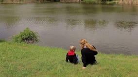 Mamman och sonen sitter på gräset på flodbanken stock video