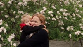 Mamman och sonen som på våren går, parkerar i en stark vind, dem kramade stramt stock video
