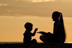 Mamman och sonen spelar på stranden silhouettes solnedgång Fotografering för Bildbyråer