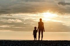 Mamman och sonen står på stranden silhouettes solnedgång Royaltyfri Fotografi