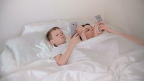 Mamman och sonen vaknar upp och bläddra internet i deras mobiltelefoner, främre sikt lager videofilmer