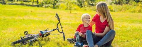Mamman och sonen vilar på gräsmattan, når de har ridit ett cykelBANER, LÅNGT FORMAT arkivfoton