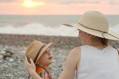 Mamman och sonen vilar på Pebblet Beach skjuten solnedgångtid för exponering long tillbaka sikt Arkivfoton