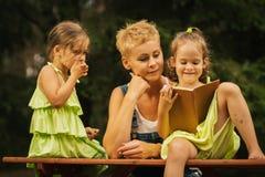 Mamman och två förtjusande döttrar läste en bok i en sommarskog Fotografering för Bildbyråer