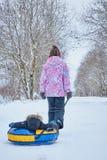 Mamman rullar hennes lilla son på rör i parkerar i vintern lycklig familj utomhus vintergyckel för unga barn fotografering för bildbyråer