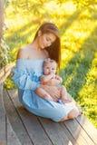 Mamman rymmer ett litet fylligt behandla som ett barn i armarna på varm ljus en utomhus- sommardag arkivfoton
