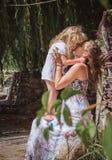 Mamman rymmer flickan på semester för handsommarstrand Royaltyfri Bild