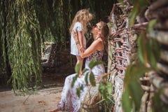 Mamman rymmer flickan på semester för handsommarstrand Arkivfoton