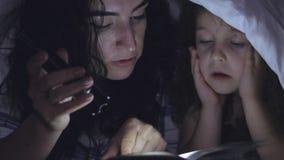 Mamman samman med lite den härliga dottern som läs med en viktig av en saga för natten, händer det i lager videofilmer