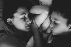 Mamman ser det sova barnet Arkivfoton