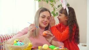 Mamman sitter på tabellen med korgar av målade ägg och drar en blå borste på ett fegt ägg Det kör dottern säger i hans stock video