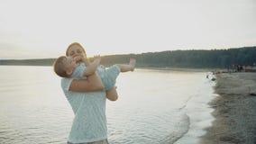 Mamman skrattar och kastar hennes dotter i henne armar stock video
