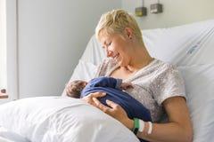 Mamman som ammar hennes nyfött, behandla som ett barn pojken i ett sjukhus Arkivbild