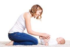 Mamman som gör övningar med ditt, behandla som ett barn på golvet Royaltyfri Foto