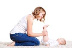 Mamman som gör övningar med ditt, behandla som ett barn på golvet Royaltyfri Bild