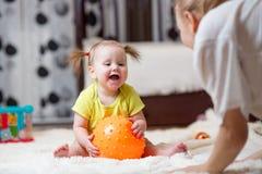 Mamman som spelar bollen med, behandla som ett barn inomhus Royaltyfria Bilder