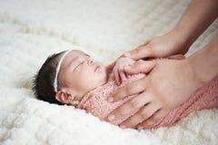 Mamman som tar omsorg av nyfött, behandla som ett barn arkivfoto
