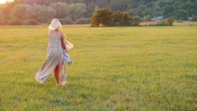 Mamman spelar med hennes dotter, vrider henne runt om henne På en härlig äng på solnedgången aktiv livsstil arkivfilmer