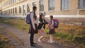 Mamman tar deras döttrar till skola på solnedgången En kvinna medföljer hennes döttrar till skola och att krama dem och efter arkivfilmer