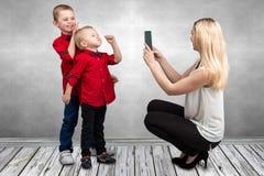Mamman tar på söner för mobiltelefon två Barn spelar gyckel och skämmer bort rolig fritid royaltyfria bilder