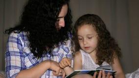 Mamman tillsammans med en liten härlig dotter, läser med en vridning av en saga för natten som kasta sig in i berättelsen av arkivfilmer