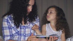 Mamman tillsammans med en liten härlig dotter, läser med en vridning av en saga för natten som kasta sig in i berättelsen av stock video