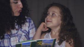 Mamman tillsammans med en liten härlig dotter, läser med en vridning av en saga för natten som kasta sig in i berättelsen av lager videofilmer