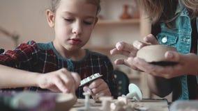 Mamman undervisar barnet hur man gör en platta av lera Hem- krukmakeri lager videofilmer