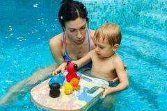 Mamman undervisar behandla som ett barn för att simma Arkivfoto