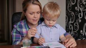 Mamman undervisar hans son att måla, närbildståenden stock video