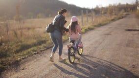 Mamman undervisar lilla flickan att rida en cykel på en varm höstafton Begreppet av en lycklig familj stock video