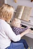Mamman undervisar lite barnet att spela pianot arkivbilder