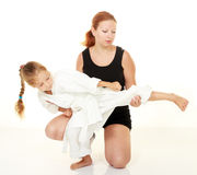 Mamman undervisar sparkande karate för dotterstansmaskin Royaltyfri Bild