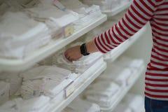 Mamman väljer nappyen, eller blöjan behandla som ett barn in shoppar arkivfoto