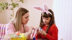 Mamman visar hennes dotter hur man målar med målarfärgpåskägg, ett med intresse och en eftertänksam sort av smaker och färger arkivfilmer