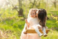 Mammarullar behandla som ett barn p? en gunga i de blomma tr?dg?rdarna eller att parkera Mors dag mars 8, v?rlynne fotografering för bildbyråer