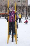Mammaservice från baksidan av barnanseendet på trästyltor på vintern Social aktivitet äger rum på Maslenitsa ferie, Ryssland royaltyfria foton