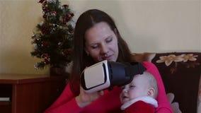 Mammaspelen met de baby masker van de vertoningen het virtuele werkelijkheid stock footage