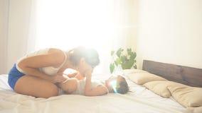 Mammaspelen met een jongen na slaap het lachen pret stock video