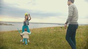 Mammaspelen met een klein kind in de bal, de kindlooppas aan haar, de balvliegen aan papa, bewolking, de zomerdag stock videobeelden