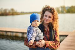 Mammatribunes bij de pijler op de rivier met haar zoon Het mamma bekijkt haar baby en glimlacht royalty-vrije stock foto's