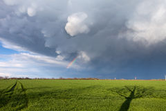 Mammatus clouds and a rainbow above a green Stock Photos