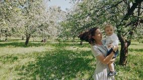 Mammavisningförälskelse och affektion till sonen Barnet fostrar och sonen som utomhus spelar arkivfilmer