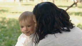 Mammavisningförälskelse och affektion till sonen Barnet fostrar och sonen som utomhus spelar stock video