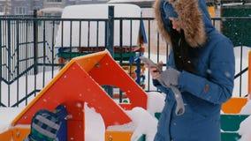 Mammavraag op een mobiele telefoon terwijl haar zoon op de speelplaats in de winter tijdens sneeuwval loopt stock video